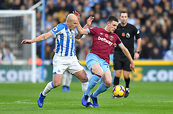Huddersfield Town's Aaron Mooy (left) and West Ham United's Declan Rice battle for the ball during the Premier League match at the John Smith's Stadium, Huddersfield.