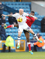 Millwall's Richard Chaplow battles for the high ball with Barnsley's Kelvin Etuhu - Photo mandatory by-line: Robin White/JMP - Tel: Mobile: 07966 386802 23/11/2013 - SPORT - Football - Millwall - The Den - Millwall v Barnsley - Sky Bet Championship