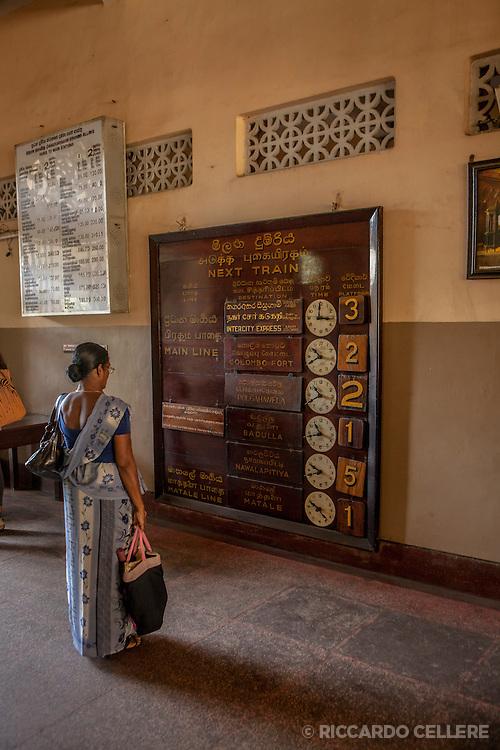 Sri Lanka. A woman checks the train schedule.