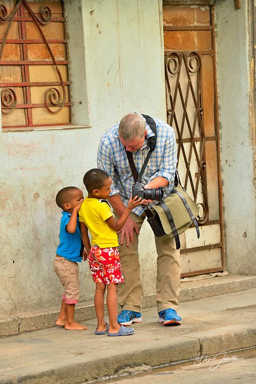 Street photography in central Havana- tourist photographing  residents along Calle Neptuno, La Habana (Havana), Habana, Cuba