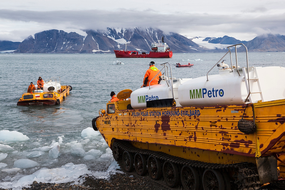 Soviet-era amphibious vehicles are used to shuttle gasoline from a delivery ship to the storage tanks on land at the Polish Polar Station in Hornsund, Svalbard. The station operates year round and uses 90,000 liters of gasoline per year to operate generators, boats, snowmobiles, and heavy machinery.