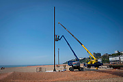 Workmen carry out the reinstallation of 'Out of Tune' by AK Dolven with a cherry picker and a crane on the 21st of May 2020 on the seafront in Folkestone, United Kingdom. This sound installation was originally part of the Folkestone Triennial Art festival of 2011.  A K Dolven's installation 'Out of Tune' features a sixteenth century tenor bell from Scraptoft Church in Leicestershire, which had been removed for not being in tune with the others. It is suspended from a steel cable strung between two 20m high steel beams, placed 30m apart. The bell was cast by Hugh Watts in the seventeenth century in Leicester. The Watts family were the leading bell founders in that city in the early 17th century. In all, they were responsible for almost two hundred castings for churches in the county. Hugh Watts prospered and was the Mayor of Leicester when King Charles 1st visited the city in 1634.