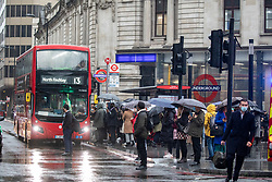 © Licensed to London News Pictures. 20/10/2020. London, UK. Large queues form at Victoria Station, London as commuters brave the wind and rain on their way to work as storm Barbara hits the UK with winds over 40mph and heavy rain. The Met Office have issue a yellow weather warning for torrential rain and flooding for the South East of England as a storm from Spain heads to the UK. Photo credit: Alex Lentati/LNP
