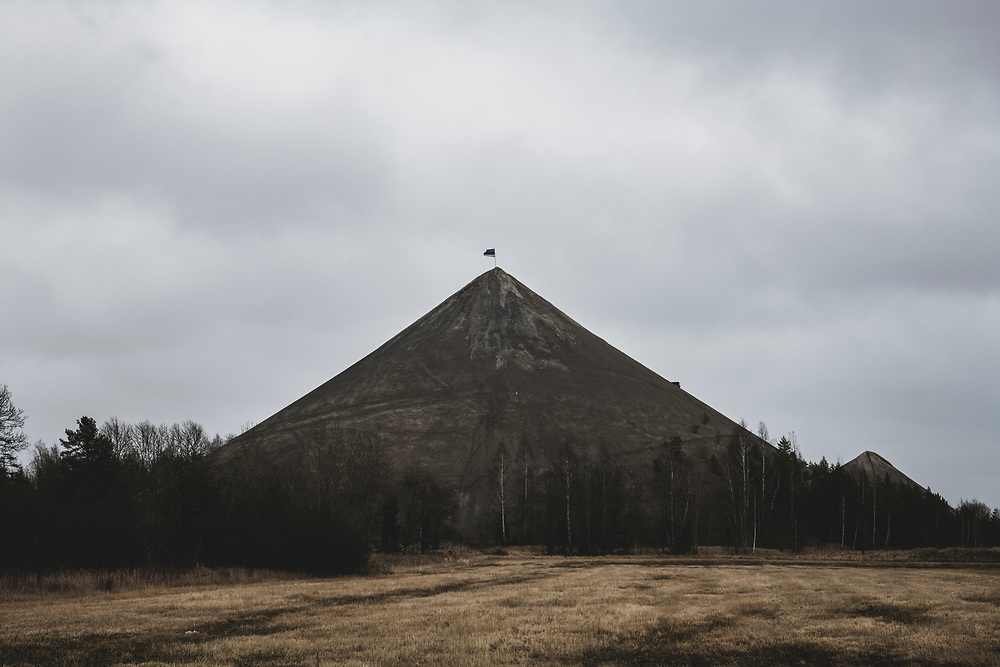 Kiviõli, Estonia - February 22, 2020: An Estonian flag flies from atop one of the many shale oil ash hills that dot the landscape in northeastern Estonia. These artificial hills are made from the waste ash produced when oil shale, a sedimentary rock that is abundant in the region, is processed into power or oil.
