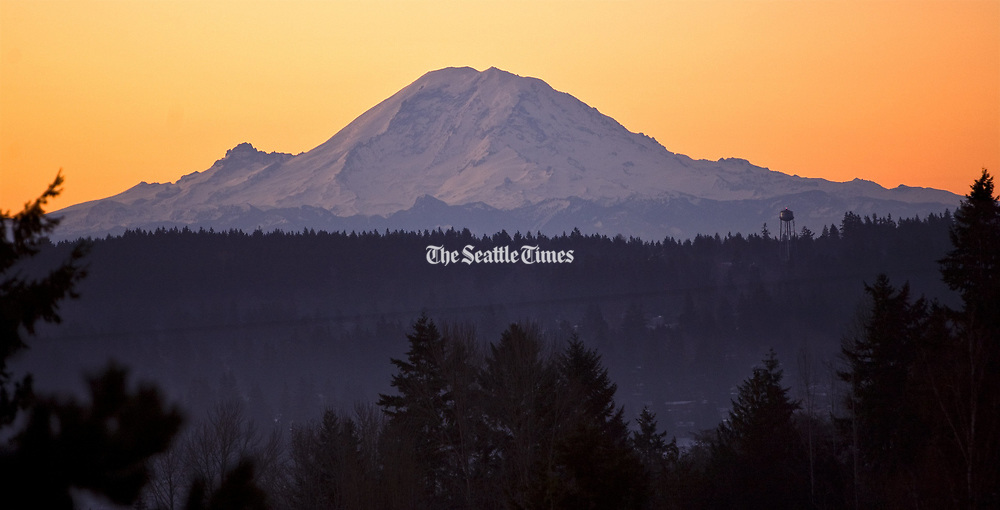 Mt. Rainier glistens in the early morning sunrise in this view from the Horizon View neighborhood of Lake Forest Park. (Mike Siegel / The Seattle Times)