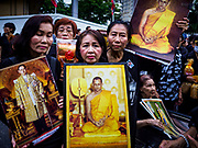 13 OCTOBER - BANGKOK, THAILAND:    Women hold portraits of the late King on the first anniversary of the death of Bhumibol Adulyadej, the Late King of Thailand. About 199 monks from 14 Buddhist temples in Bangkok participated in the mass merit making at Siriraj Hospital to mark the anniversary of the revered King's death. He will be cremated on 26 October 2017.  PHOTO BY JACK KURTZ