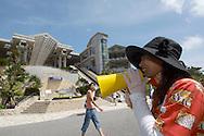 JPN, Japan: Okinawa Churaumi Aquarium, mit Hilfe eines Megaphones werden die Besucher in die richtige Richtung dirigiert, Ocean Expa Park, Okinawa, Okinawa | JPN, Japan: Okinawa Churaumi Aquarium, woman using a megaphone to directing the visitors in the right direction, Ocean Expo Park, Okinawa, Okinawa |