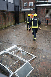 © Licensed to London News Pictures. 04/03/2018. Harold Hill, UK. Firefighters pass the remains of a window as they enter the back yard of Harold Hill Post Office where emergency services are currently responding to reports of an explosion. Nearby homes have been evacuated. Photo credit: Peter Macdiarmid/LNP