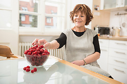 Senior woman nibbling raspberries in the kitchen, Munich, Bavaria, Germany