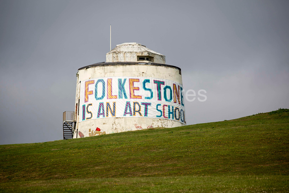 A Folkestone is an Art School banner, attached to Folkestone's most prominent Martello Tower on the east cliff. The banner has been designed by the artist Bob and Roberta Smith as part of the 2017 Folkestone Triennial. Folkestone, Kent.