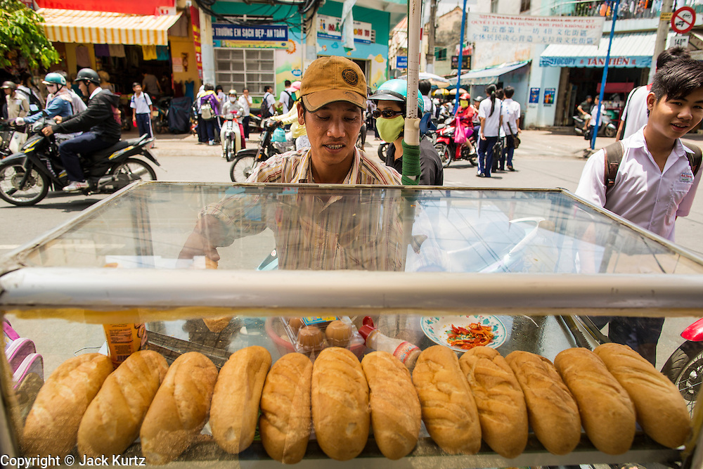 """12 APRIL 2012 - HO CHI MINH CITY, VIETNAM:  A sandwich vendor sells lunch sandwiches on a street in Cholon, the Chinese-influenced section of Ho Chi Minh City (former Saigon). It is the largest """"Chinatown"""" in Vietnam. Cholon consists of the western half of District 5 as well as several adjoining neighborhoods in District 6. The Vietnamese name Cholon literally means """"big"""" (lon) """"market"""" (cho). Incorporated in 1879 as a city 11km from central Saigon. By the 1930s, it had expanded to the city limit of Saigon. On April 27, 1931, French colonial authorities merged the two cities to form Saigon-Cholon. In 1956, """"Cholon"""" was dropped from the name and the city became known as Saigon. During the Vietnam War (called the American War by the Vietnamese), soldiers and deserters from the United States Army maintained a thriving black market in Cholon, trading in various American and especially U.S Army-issue items.         PHOTO BY JACK KURTZ"""