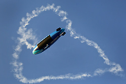 02 May 2015. New Orleans, Louisiana.<br /> The New Orleans Jazz and Heritage Festival. <br /> The DIRECTV blimp passes underneath a sky writer's heart in the sky. I love DIRECTV.<br /> Photo; Charlie Varley/varleypix.com
