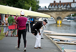 © London News Pictures. 03/07/2013.  Henley-on-Thames, UK. An elderly man wearing rowing colours ducks underneath a passing boat during  Day one of Henley Royal Regatta on the River Thames at Henley-on-Thames, Oxfordshire on July 03, 2013. Photo credit: Ben Cawthra/LNP