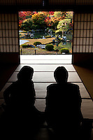 Couple admiring the view from tatami room at Tenryu-ji Temple's Sogenchi Pond Garden. Tenryuji is more formally known as Tenryu Shiseizen-ji and is the head temple of the Tenryu branch of Rinzai Zen Buddhism. Its first chief priest was Muso Soseki the famous Zen garden designer who created this magnificent garden which was named a UNESCO World Heritage Site.