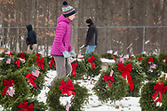Goshen, New York - A girl carries American flags during a Wreaths Across America ceremony at Orange County Veterans Memorial Cemetery on Dec. 16, 2017. About 3,000 wreaths were placed at graves, and small American flags were added to the wreaths at veterans' graves.