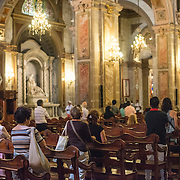 Some of the congregation gathered for Sunday mass in the Metropolitan Cathedral of Santiago (Catedral Metropolitana de Santiago) in the heart of Santiago, Chile, facing Plaza de Armas. The original cathedral was constructed during the period 1748 to 1800 (with subsequent alterations) of a neoclassical design.