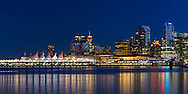 Canada Place, the Trade and Convention Center and other downtown buildings reflect on the water of Coal Harbour in Vancouver, British Columbia, Canada
