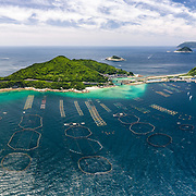 This is an aerial view of the small island of Kashiwa-jima in Kochi Prefecture, Japan, visible here connected to the mainland by a small bridge. Kashiwa-jima is a fishing community, and is also popular among recreational scuba divers. The pens in the foreground are for aquaculture. The large pens hold tuna.