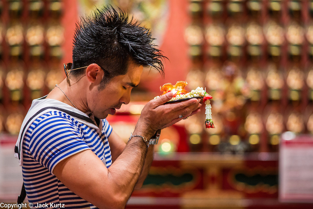 "16 DECEMBER 2012 - SINGAPORE, SINGAPORE:  A man prays at the Buddha Tooth Relic Temple and Museum in the Chinatown section of Singapore. The temple houses a sacred Buddha tooth relic. It is a ""Mahayana"" Buddhist temple, the larger of the two Buddhist sects. Mahayana Buddhism is practiced in India, China, Vietnam (northern), Japan, Tibet, Mongolia, Korea and in Chinese immigrant communities around the world.      PHOTO BY JACK KURTZ"
