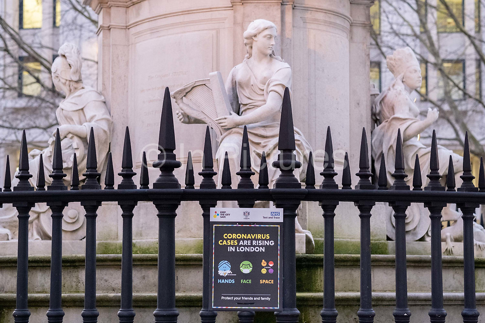 A government warning sign urging Londoners to observe Covid restriction laws a hygiene guidance, is attached to the railings of the Queen Anne Statue in front of St Pauls Cathedral in the City of London, on 26th February 2021, in London, England. The statues are a copy of a 1712 sculpture by Francis Bird in Carrara marble which formerly stood at the same location. Queen Anne was the ruling British monarch when the new St Pauls Cathedral was completed in 1710.