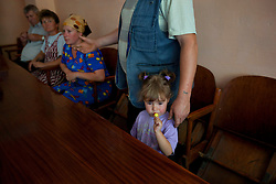 Left to right, Fedir Kucher, 72, Tamara Sovenko and Ljudmila Kashpirovska listen as Olexander Chuzha voices his concerns about the dangers of high voltage power lines in close proximity to their homes, Bila Tserkva, Ukraine, June 14, 2011. His daughter Katerina Cherednichenko, 3, has a candy while he looks for legal advice at the village community center. More than half of the worldÕs population, four billion people, live outside the rule of law, with no effective title to property, access to courts or redress for official abuse. The Open Society Justice Initiative is involved in building capacity and developing pilot programs through the use of community-based advocates and paralegals in Sierra Leone, Ukraine and Indonesia. The pilot programs, which combine education with grassroots tools to provide concrete solutions to instances of injustice, help give poor people some measure of control over their lives.