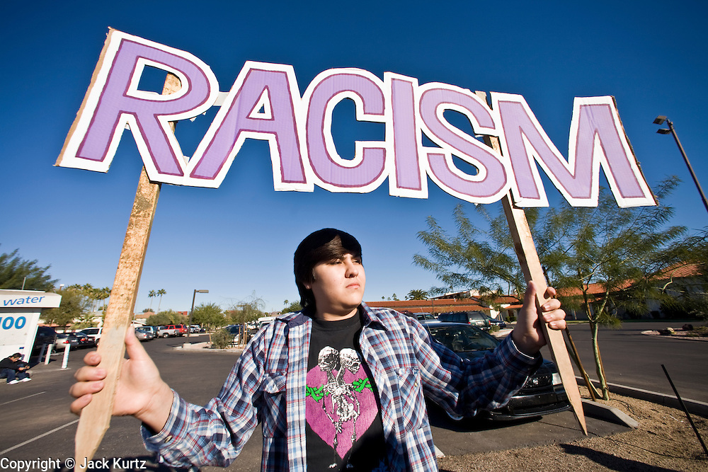 """15 DECEMBER 2007 -- PHOENIX, AZ: ULISES LARA, from Phoenix, holds a pro immigrant sign during an immigration rally in Phoenix, AZ. The corner of 35th Street and Thomas Road in Phoenix has emerged as """"Ground Zero"""" in the immigration debate in Arizona. A furniture store at the intersection has hired off duty sheriff's deputies to arrest day laborers who used to gather near there for loitering. Pro immigrant groups have labored the move racist while anti-immigrant groups call it law abiding and patriotic. Every week, hundreds of people gather on opposite corners of the intersection to chant and hurl insults at each other.  Photo by Jack Kurtz"""