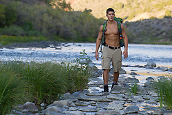 shirtless good looking young man hiking along The Rio Grande in New Mexico