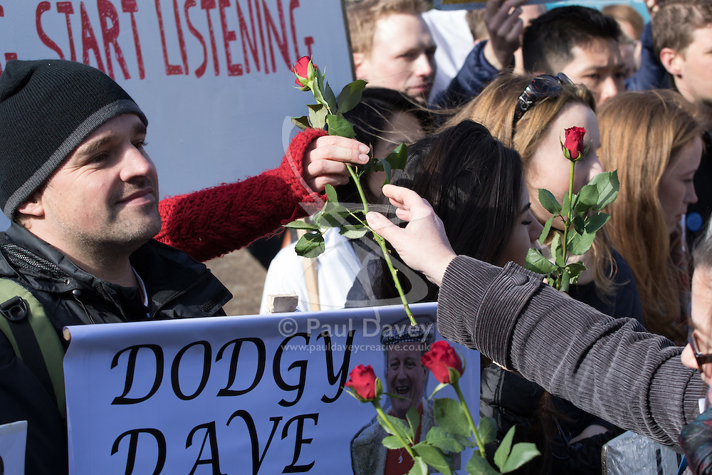 St Thomas' Hospital, London, April 26th 2016. A woman hands out roses to striking junior doctors picketing St Thomas' hospital as they strike again against new contracts imposed on them by the Department of Health. ©Paul Davey<br /> FOR LICENCING CONTACT: Paul Davey +44 (0) 7966 016 296 paul@pauldaveycreative.co.uk