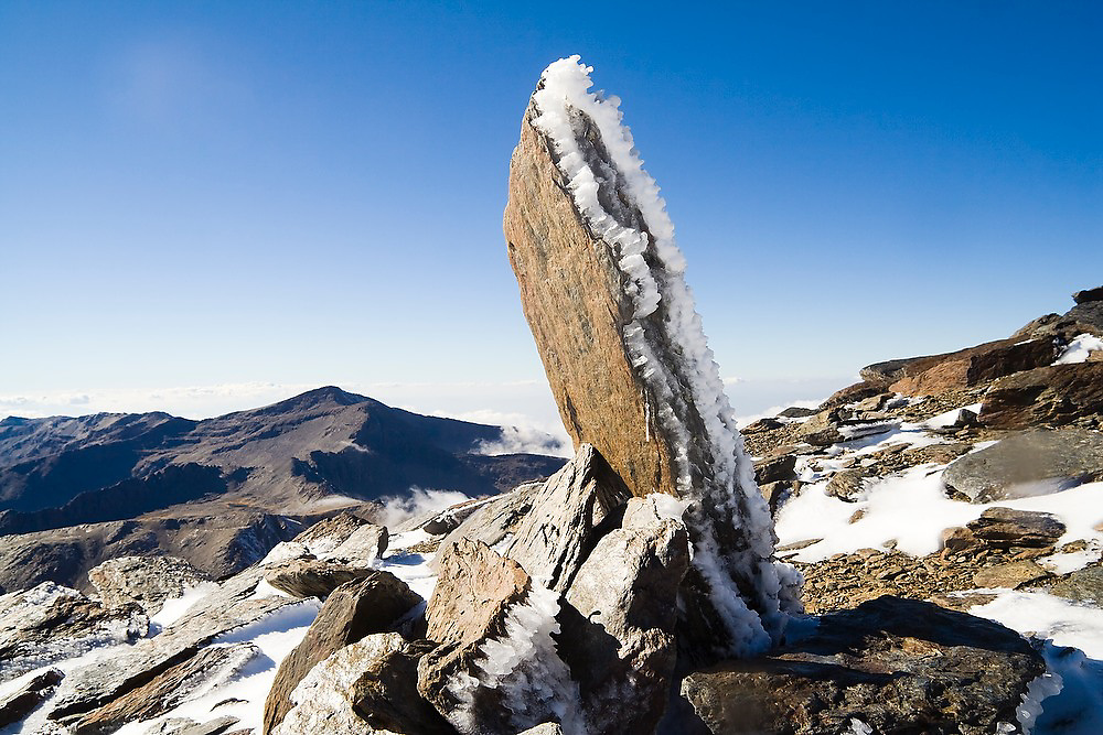 An upright stone, placed as a cairn, covered in hoar frost on the summit of Mulhacen in Sierra Nevada National Park, Andalusia, Spain. Mulhacen is the highest mountain in continental Spain and in the Iberian Peninsula.