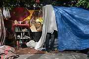 """An unhoused man sits on his bed in San Francisco, CA on June 26, 2020 before being forced to move to another street. The City of San Francisco required homeless residents to relocate to other homeless encampments or hotels, in select cases, after the University of California Hastings School of Law filed a suit against the City, declaring """"dangerous and illegal conditions in the Tenderloin neighborhood."""""""