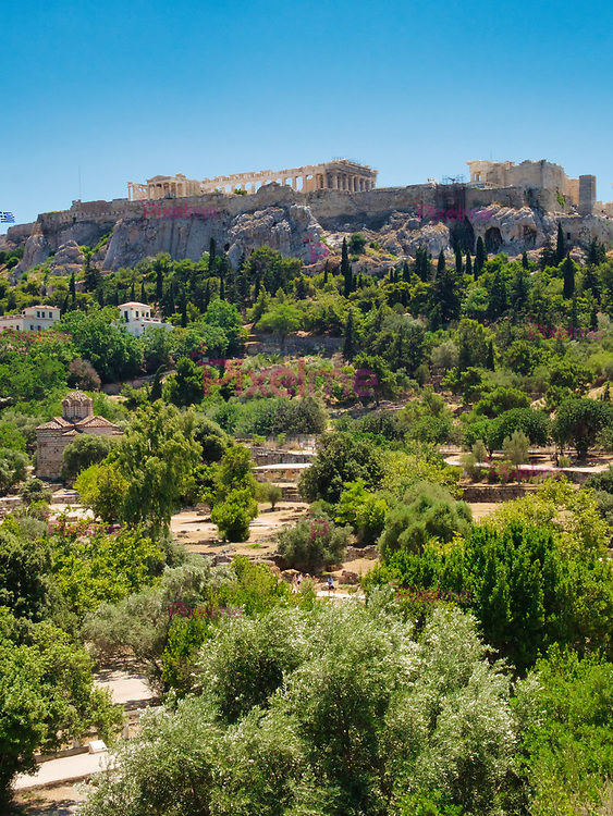 View from Ancient Agora of Athens on Acropolis landmark among ancient ruins and green trees in sunlight