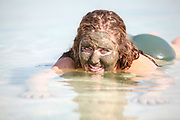 Mud covered Caucasian tourist floats in the Dead Sea, Israel