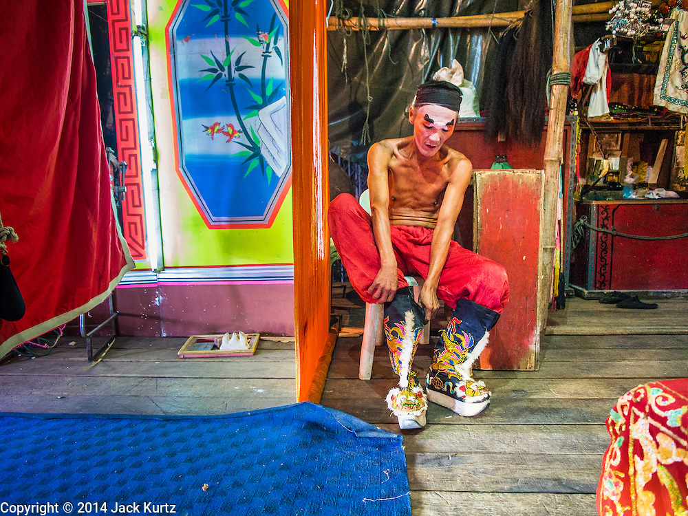 "18 AUGUST 2014 - BANGKOK, THAILAND: A member of the Lehigh Leng Kaitoung Opera troupe puts on his boots before a performance at Chaomae Thapthim Shrine, a small Chinese shrine in a working class neighborhood of Bangkok. The performance was for Ghost Month. Chinese opera was once very popular in Thailand, where it is called ""Ngiew."" It is usually performed in the Teochew language. Millions of Chinese emigrated to Thailand (then Siam) in the 18th and 19th centuries and brought their culture with them. Recently the popularity of ngiew has faded as people turn to performances of opera on DVD or movies. There are still as many 30 Chinese opera troupes left in Bangkok and its environs. They are especially busy during Chinese New Year and Chinese holiday when they travel from Chinese temple to Chinese temple performing on stages they put up in streets near the temple, sometimes sleeping on hammocks they sling under their stage. Most of the Chinese operas from Bangkok travel to Malaysia for Ghost Month, leaving just a few to perform in Bangkok.      PHOTO BY JACK KURTZ"