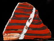 Banded red jasper and dark hematite with white quartz vein following reverse fault, Australia.