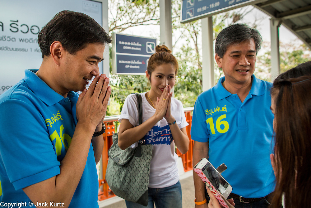 16 FEBRUARY 2013 - BANGKOK, THAILAND:  ABHISIT VEJJAJIVA, former Prime Minister of Thailand, greets voters as he walks into the MoChit BTS station to campaign for his party colleague Sukhumbhand Paribatra ahead of Bangkok's governor election. Bangkok residents go to the polls on March 3 to elect a new governor. Sukhumbhand Paribatra, the current governor, is running on the Democrat's ticket and is getting help from national politicians like Abhisit Vejjajiva, the former Thai Prime Minister. One of Sukhumbhand's campaign pledges is to improve Bangkok's mass transit and transportation system. Abhisist road the BTS Skytrain to campaign for Sukhumbhand.     PHOTO BY JACK KURTZ