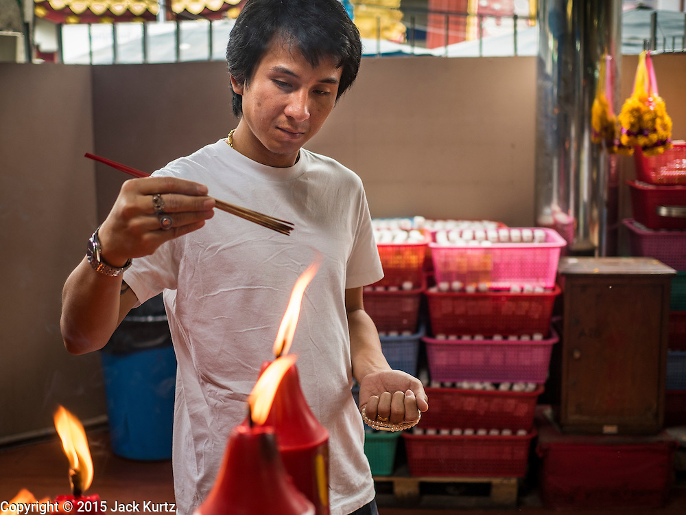 28 AUGUST 2015 - BANGKOK, THAILAND: A man lights incense at the Poh Teck Tung shrine in the Chinatown section of Bangkok on Hungry Ghost Day. Mahayana  Buddhists believe that the gates of hell are opened on the full moon of the seventh lunar month of the Chinese calendar, and the spirits of hungry ghosts allowed to roam the earth. These ghosts need food and merit to find their way back to their own. People help by offering food, paper money, candles and flowers, making merit of their own in the process. Hungry Ghost Day is observed in communities with a large ethnic Chinese population, like Bangkok's Chinatown.     PHOTO BY JACK KURTZ