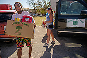 18 AUGUST 2020 - CEDAR RAPIDS, IOWA: Refugees from Congo pick up relief supplies provided by Central Church of Christ at Cedar Terrace Apartments in Cedar Rapids. The complex was destroyed by the derecho wind storm and the people who have stayed don't have running water or electricity. Most of the tenants in the complex are refugees from Africa and Micronesia who have chosen the camp in front of the buildings rather than move to shelters because they're worried about looters taking their belongings. Cedar Rapids was the state's hardest hit city by the derecho that roared across Iowa last week. City officials said the damage left by the derecho was more extensive than the 2008 flood that destroyed much of its downtown. City residents are reporting that almost every home was damaged in the storm, many businesses were closed, and up to half of the city's tree canopy was destroyed. A week after the storm, more than 40,000 homes were still without power. A spokesman for Alliant Energy said the utility has replaced as many power poles in one week that they normally replace in 8 months. On Monday, President Trump approved a $4 billion emergency declaration for Iowa to aid in derecho recovery.     PHOTO BY JACK KURTZ
