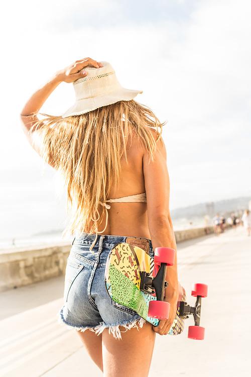 Beach babe walking down the boardwalk with a skateboard.