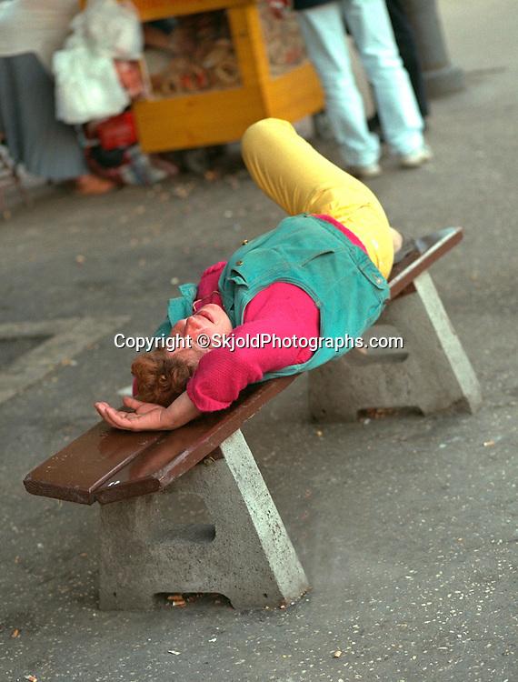 Woman age 50 resting on city bench.  Krakow Poland