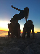 Children do acrobatics on beach at sunset, Cape May