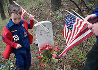 Matthew Lamb, 7, and his father, Dennis, place flags on veterans' gravesites Saturday at Aspen Hills Cemetery. Dennis Lamb and other members of the American Legion Post 43 spent the afternoon honoring local veterans' gravesites for the Memorial Day weekend.