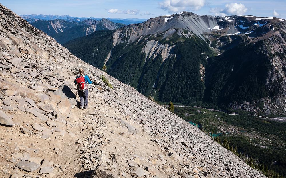 A woman on Burroughs mountain trail heading down on a trail across a talus field, Mount Rainier National Park, Washington, USA.