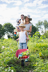 Family walking with wheelbarrow in community garden, Bavaria, Germany