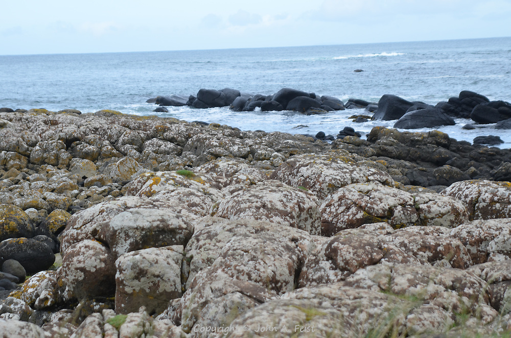 Salt covered rocks, basalt boulders and waves coming into the Giant's Causeway, County Antrim, Northern Ireland.