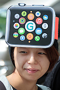 Makoto Saito wears an Apple watch hat as she waits to buy the product on its officail release at the Softbank Store in Omotesando, Tokyo, Japan. Friday April 24th 2015. Apple's long anticipated  smart watch was officially put on sale in stores in just nine countries. Japan and Australia which are furthest east were the first places in the world where this watch was available for purchase.