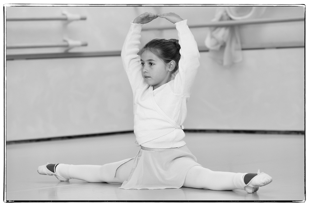 Cute little girl during a classical dance course, doing the splits