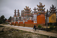 """Vietnamese man cycling near a tomb in the """"ghost city"""", Hue area, Vietnam, Southeast Asia"""