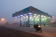 New Lucky 7 fuel station in fog with motorcycle blurring by, Aung Ban
