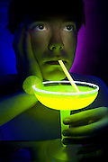 Young man drinking a margarita through a golden glowing straw.Black light