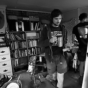 Gray and Noel eat breakfast before heading out to pread lime over felids at Circle Acres farm. Books about farming and agriculture fill the shelves behind him. The group has rigged up an makeshift circuit board, which powers an oven, some lights and a radio, but does not have indoor plumbing.